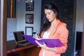 Businesswoman writing in notebook — Stockfoto