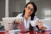 Kobieta siedzi na biurku — Zdjęcie stockowe