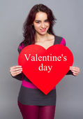 Smiling girl holding paper heart — Stock Photo