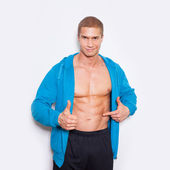 Muscled man poiting at torso — Stockfoto
