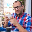 Man with mobile phone in restaurant — Stock Photo