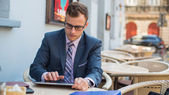 Businessman using tablet in cafe — Stock Photo