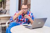 Hombre con portátil y café — Foto de Stock