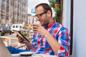 Man using tablet and drinking coffee — Stock Photo