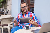 Man using tablet and mobile phone — Stockfoto