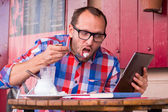 Man eating and using tablet — Foto de Stock