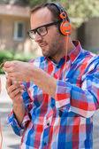 Muž, poslech hudby na mobilním telefonu — Stock fotografie