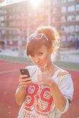 Girl holding phone and showing thumb up — Stock Photo