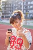 Dziewczyna trzyma telefon i wyświetlone kciuka — Zdjęcie stockowe