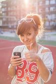 Ragazza alzando telefono e mostrando pollice — Foto Stock