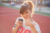 Girl with phone showing thumb up — Stock Photo