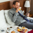 Businessman using tablet during breakfast — Stock Photo