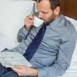 Businessman drinking coffee and reading newspaper — Stock Photo