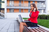 Young girl with laptop and mobile phone — Foto Stock