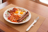 Fried eggs, sausages, beans and bacon — Stock Photo