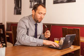 Businessman having lunch and using laptop — Stock Photo
