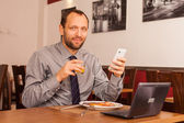 Businessman eating and using phone — Stock Photo