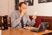 Businessman using phone while eating — Stock Photo