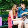 Couple sitting on bench and using digital gadgets — Stock Photo