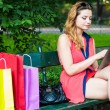 Woman sitting on bench and using tablet — Stock Photo #45093419
