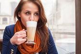 Girl drinking latte — Stock Photo