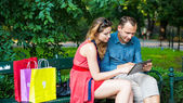 Couple sitting on bench with bags and tablet — Stock Photo