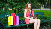 Woman sitting on bench with tablet — Stock Photo