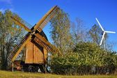 A historic windmill and a wind turbine — 图库照片