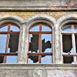 Broken windows in an abandoned house - Stock Photo