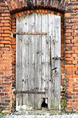 An old wooden door in a disused factory building — Stock Photo