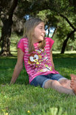 Girl Sitting In Grass Smiling — Stock Photo
