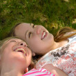Girls lying on the ground laughing — Stock Photo #24916899