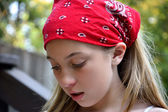 Sad adolescent girl wearing red bandana — Stock Photo