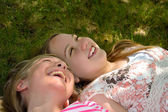 Girls lying on the ground laughing — Stock Photo