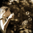 Royalty-Free Stock Photo: Young Girl Blowing Bubbles In Park