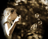 Young Girl Blowing Bubbles In Park — Stock Photo