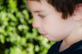 A picture of a boys face while coloring outdoors. — Stock Photo