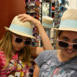 Girls playing dress up in store with hats and sunglasses — Stock Photo #26108455