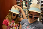 Girls playing dress up in store with hats and sunglasses — 图库照片