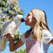 Cockatoo bird eating from girls mouth — Stock Photo