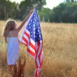 Girl walking in golden field holding American flag — Stock Photo