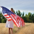 Girl holding American flag walking in golden field — Stock Photo #26819307