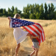 Boy and girl playing holding American flag banner — Stock Photo