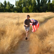 Stock Photo: Boy running through golden field holding American banner flag