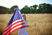 Girl holding American flag walking in golden field — Stock Photo