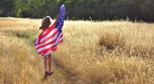 Girl running in golden field holding American flag — Stock Photo