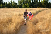 Boy running through golden field holding American banner flag — Stock Photo
