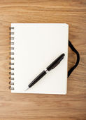 Recycled paper notebook with black elastic band and pen — Stock Photo