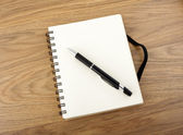 Recycled paper notebook with black elastic band and pen  — Zdjęcie stockowe