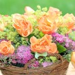 Flower basket with roses and spiraea in the garden — Stock Photo #22175717